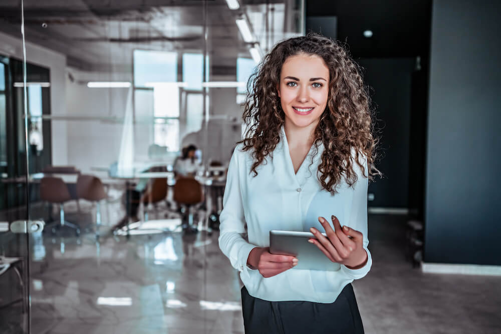 lady holding tablet and smiling in an office space while looking directly at the camera